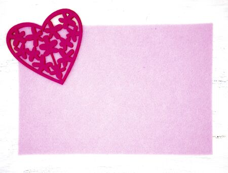 Bright crimson carved a heart out of felt on a pink background with a white border.
