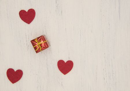 Three bright red hearts and gift box on a light wooden background. Copy space, top view