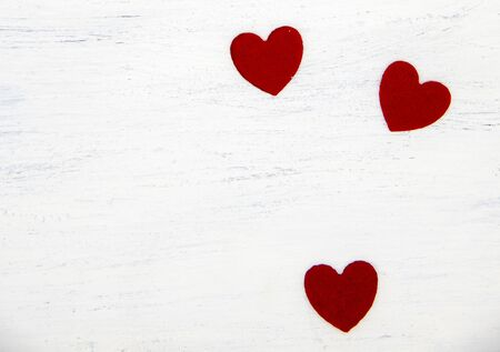 Three bright red hearts on a light wooden background. Copy space, top view