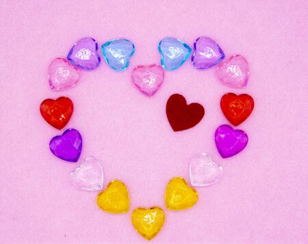 Small glass colored hearts are arranged on a pink background in the shape of one large heart.