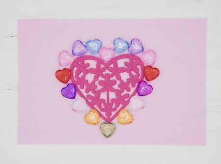 Bright heart made of felt and colored glass on a pink background in a light frame.