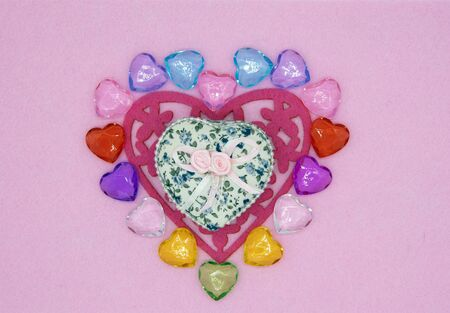 Bright heart made of felt and colored glass and a gift box on a pink background in a light frame. Banco de Imagens