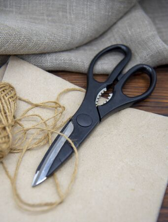 Tools for crafts on a wooden table top. Scissors, coarse thread and craft paper. Stock fotó - 138165060