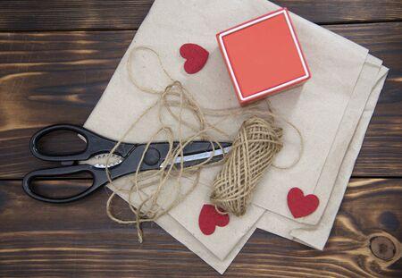 Scissors, coarse thread, and a gift box lie on Kraft paper on a dark wooden background.