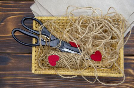 A wicker basket with scissors, coarse thread, and red felt hearts stands on Kraft paper against a dark wooden background.