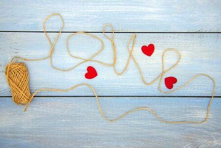 The word love is written using coarse threads and red hearts on a blue wooden background.