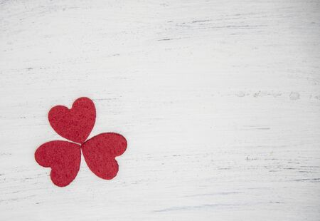 Three red hearts forming a clover leaf on a light wooden background.