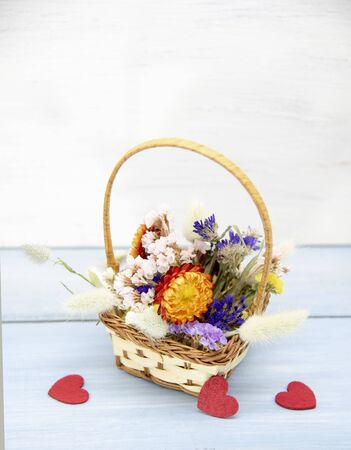 A basket of dried flowers and red hearts on a blue tabletop on light background