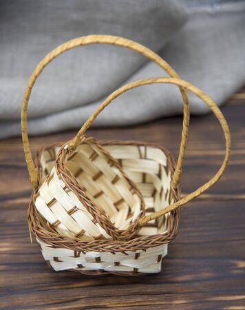 Two empty wicker small baskets, standing one in the other, on a wooden table top . Banco de Imagens