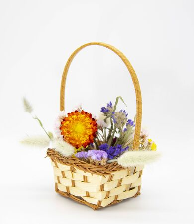 Wicker basket with bright colored dried flowers on a light background.
