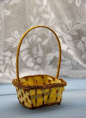 An empty wicker basket on a blue wooden table top against a white lace curtain.
