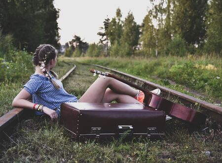 A teenage girl is sitting on the rails with a guitar and an old suitcase turned away from the camera. Reklamní fotografie