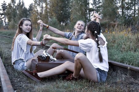 Russia, Tuchkovo village, August 2018. Three teenage girls sit on railway tracks with a vintage suitcase, a camera and a guitar. Editorial