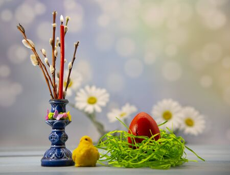 Easter card. A painted egg in a nest, willow branches and a candle on a blurred background.
