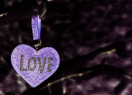 A delicate lilac heart with the inscription love on an abstract blurred dark background.