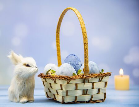 A bunny next to a basket full of Easter eggs on a wooden table on a blurred background. Burning candles in the background. 写真素材