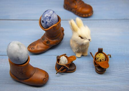 Bunny and various boots with painted Easter eggs on a blue wooden surface