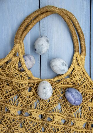 Painted blue Easter eggs in a wicker bag made of eco-friendly materials on a blue wooden background.