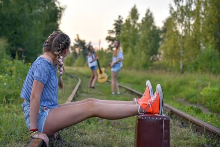 A teenage girl sits on the railway tracks with her feet on a large suitcase and looks into the distance at her friends leaving.