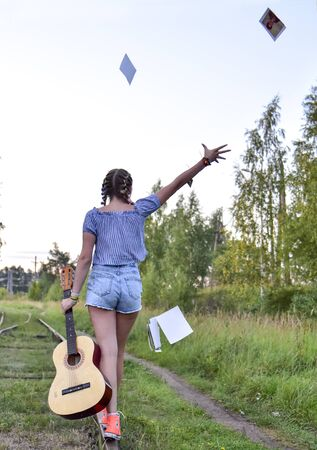 Russia, Tuchkovo village, August 2018.A teenage girl walks along the railway tracks with a guitar in her hands and throws old photos.