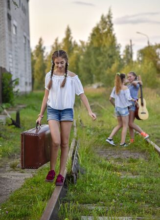 Russia, Tuchkovo village, August 2018. In the foreground, a teenage girl with an old suitcase walks along the railway tracks, her friends in the background. Redactioneel