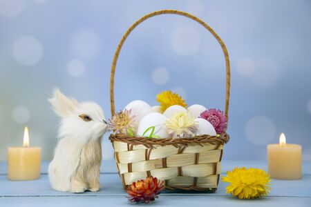The Easter Bunny sits next to a basket full of eggs, decorated with dried flowers. Burning candles in the background. Blurred background.