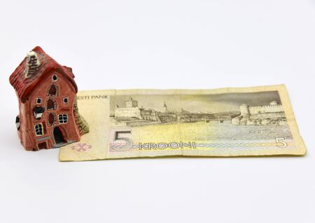 A small ceramic house stands on a disused Estonian five-kroner banknote.An Old paper banknote, vintage retro.  版權商用圖片