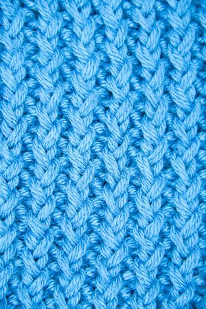 The texture of a knitted woolen fabric blue. Vertical classic blue background pattern. Copy space for text. Design. Cover