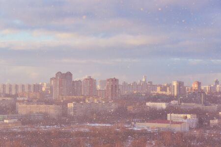 A blurred silhouette of a big city through a shroud of snow.The sun breaks through thick clouds.