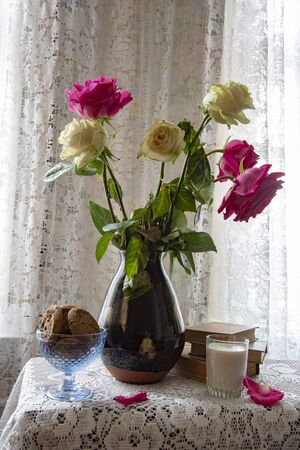 A bouquet of roses in a vintage vase on a lace tablecloth , next to books, a glass of milk and a bowl of cookies.