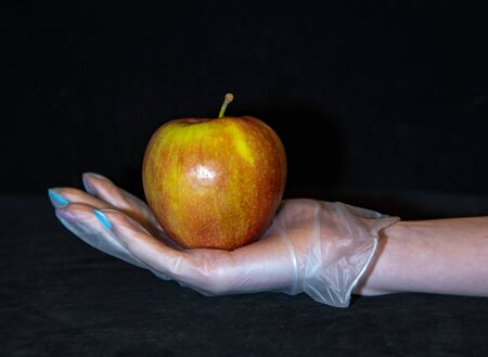 A red ripe Apple is lying on a woman's hand in a transparent rubber glove. Preventive measures for coronavirus.