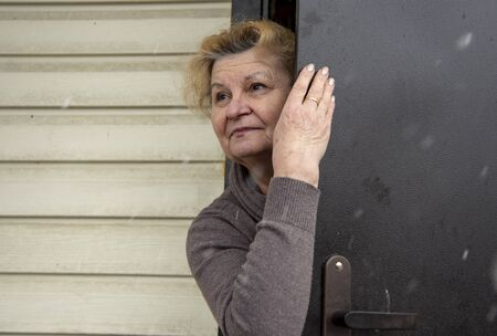 An elegant old woman looks out of a door that is slightly open. Quarantine due to the coronavirus epidemic, stay at home.