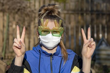 Portrait of a Girl in funny sunglasses and a medical protective mask. The girl gestures that everything will be fine. Focus on the hands. 写真素材