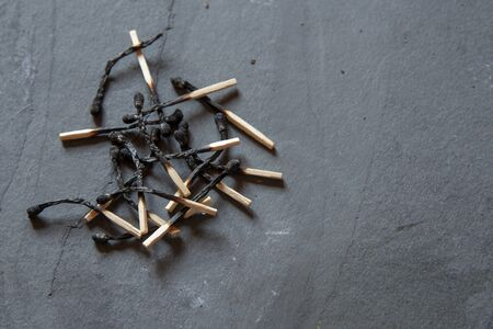 A lot of burnt matches on a slate gray background.