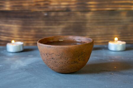 A ceramic bowl with tea and burning candles on a gray tabletop.