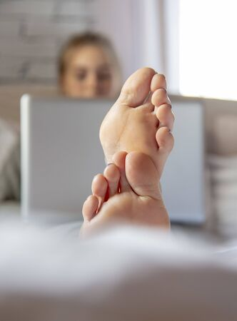 Focus on the feet in the foreground. A teenage girl is lying on a bed with a laptop. Distance learning.