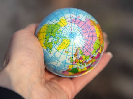 A small globe lies in a woman's hand, illuminated by the sun. Blurred background.