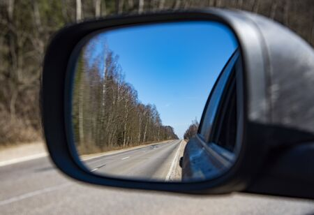 Reflection of the road in the side mirror of the car. Travel, sightseeing. Standard-Bild