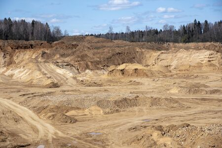 Sand deep quarry under a blue cloudy sky. Construction industry, mining. Stock Photo