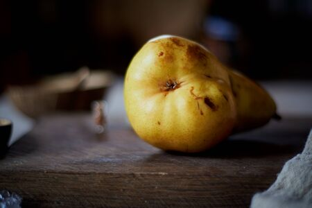 A bright yellow pear on a wooden background. Natural products, eco-friendly materials. 版權商用圖片