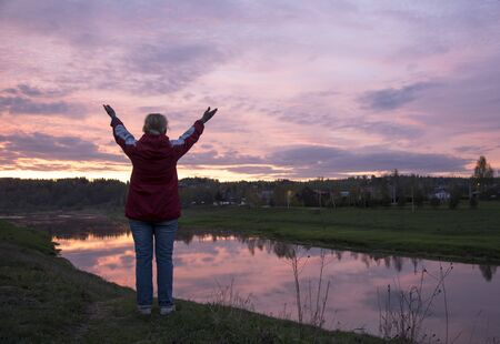 Photo of a woman standing on a hill above a river, against a bright sunset. The woman raises her hands to the sky.
