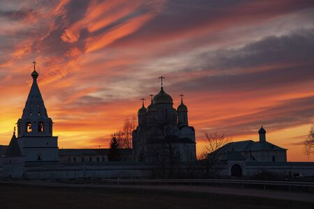 The black silhouette of the monastery against the bright sunset sky. Evening fascinating fantastic landscape.