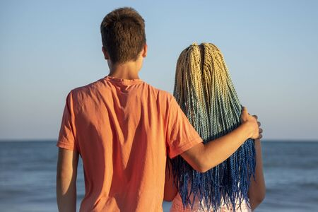 Two teenagers embracing stand with his back to the camera and look at the waves crashing on the rocks.The spray flies in all directions.The girl with the blue Senegalese braids. Stock fotó