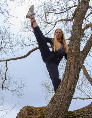 A teenage girl with long blond hair stands on a tree and does stretching exercises.