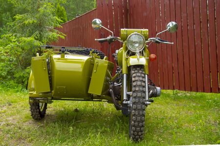 Restored green retro motorcycle with sidecar on the background of nature. Stok Fotoğraf