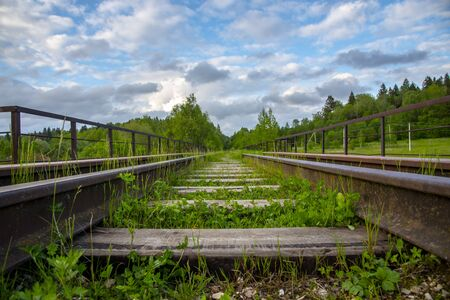 An old Abandoned railway, overgrown with green grass. Picturesque industrial landscape. Rails going into the distance.