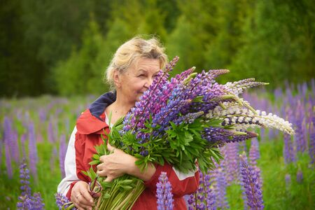 An older woman stands against a green forest with a huge bouquet of bright lupins.