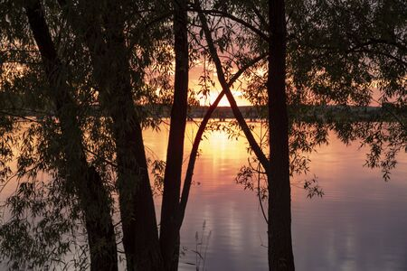 A magnificent bright orange sunset over the lake was photographed through the trees. summer evening landscape.