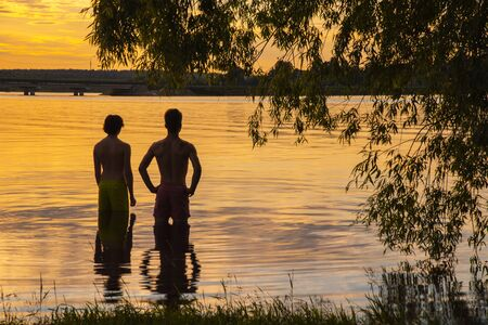 Silhouettes of two young men against the background of water, colored by the sunset. Summer evening landscape. 版權商用圖片