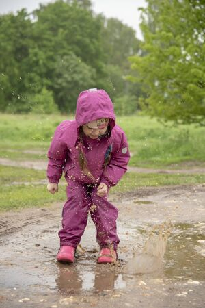 A little girl in a pink jumpsuit jumps in a puddle and splashes fly in all directions. Standard-Bild